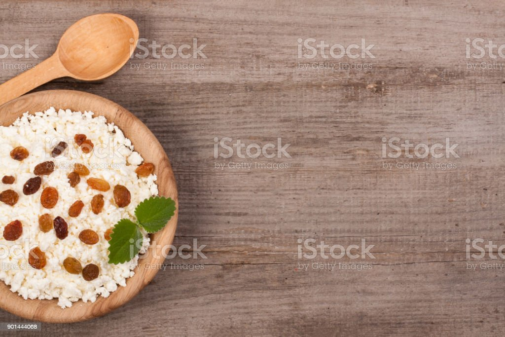 Cottage cheese with raisins in a wooden bowl on old wooden background with copy space for your text. Top view stock photo
