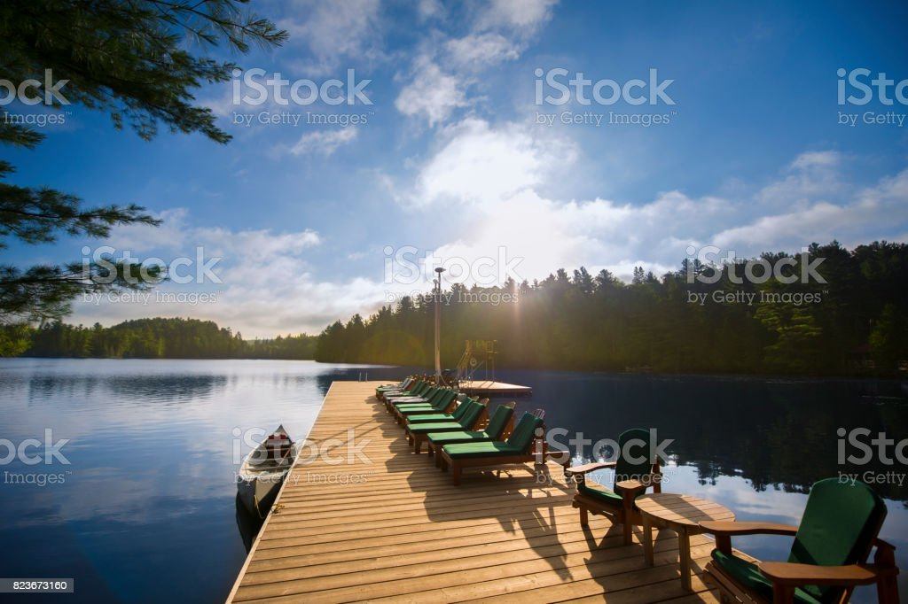 Cottage life - Chairs on a dock during sunrise stock photo