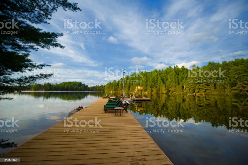 Cottage life - Lounge chairs on a wood dock stock photo