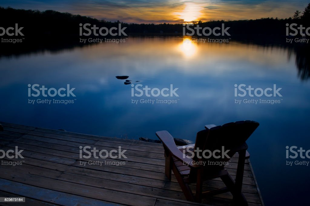 Cottage life, Muskoka chair facing water at sunset stock photo