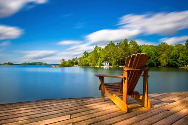 cottage life - muskoka chair - lake stock photos and pictures