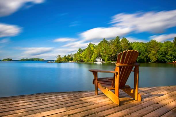 cottage leben - muskoka stuhl - see stock-fotos und bilder