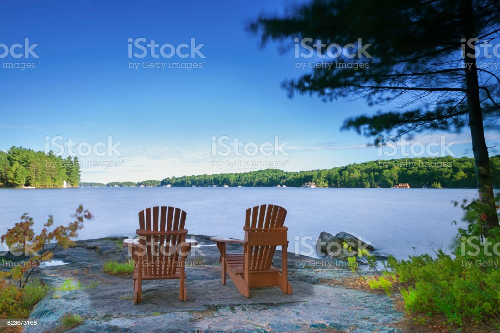 Cottage life - Muskoka chairs facing a lake stock photo