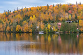 Cottage in the forest on the lake in Canada, during the Indian summer, beautiful colors of the trees in Charlevoix area
