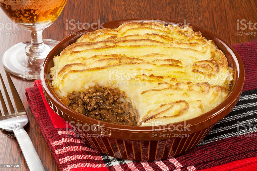 Cottage pie in a brown dish next to a fork and glass of wine stock photo