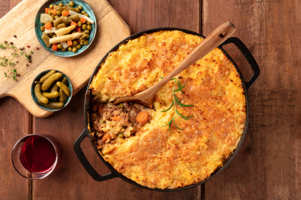 Cottage pie with pickles and red wine, top shot on a dark rustic wooden background stock photo