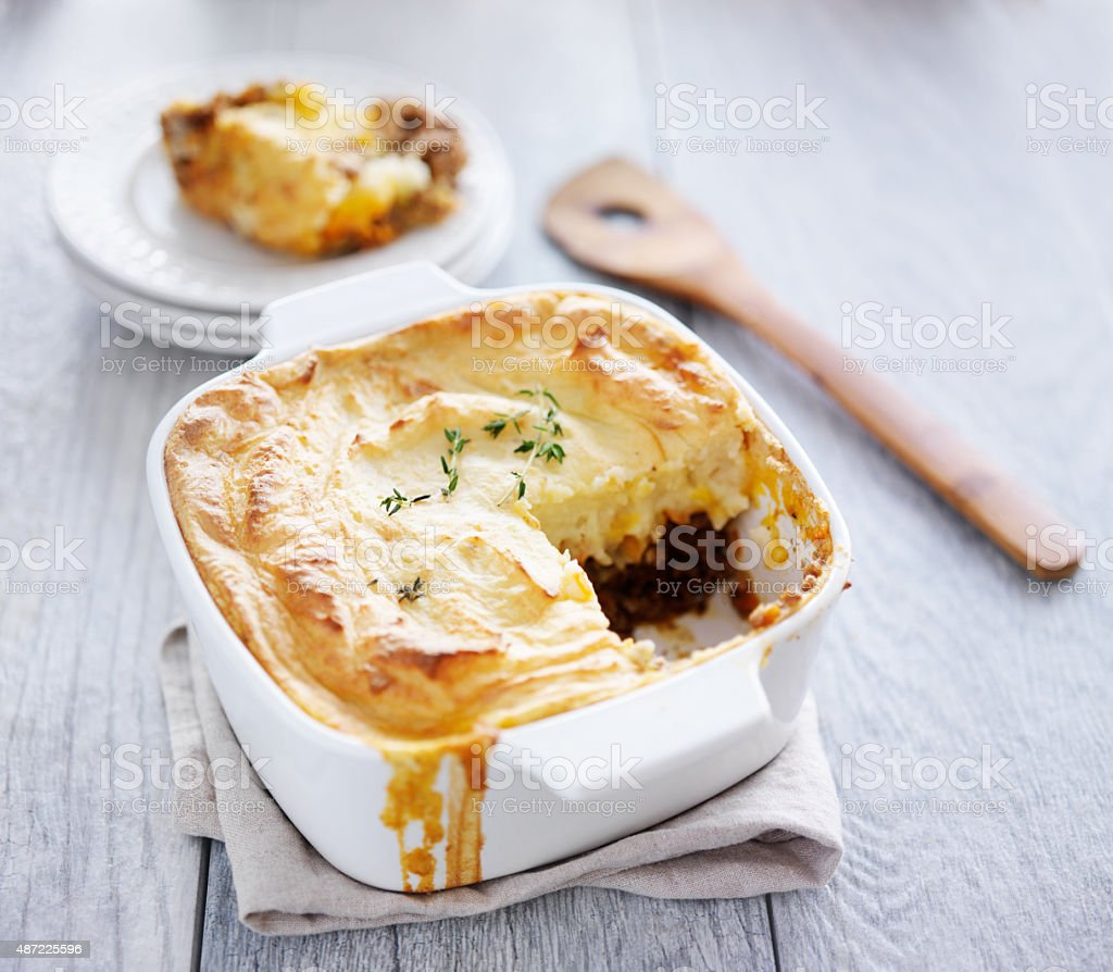cottage pie with piece missing and served on plate stock photo