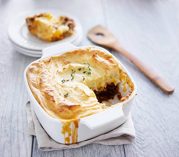 cottage pie mit stück fehlt und serviert auf platte - gemüseauflauf mit hackfleisch stock-fotos und bilder