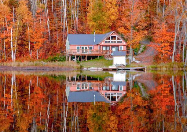 gölde sonbaharda yansıtan yazlık - kır evi stok fotoğraflar ve resimler