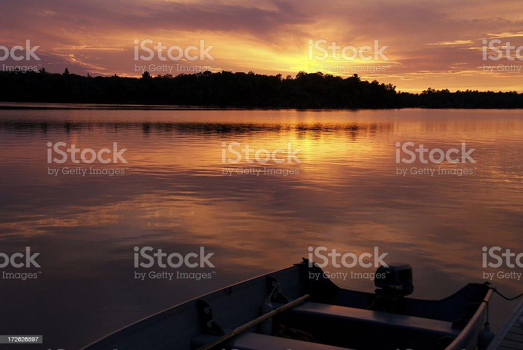 Cottage Sunset with fishing boat stock photo