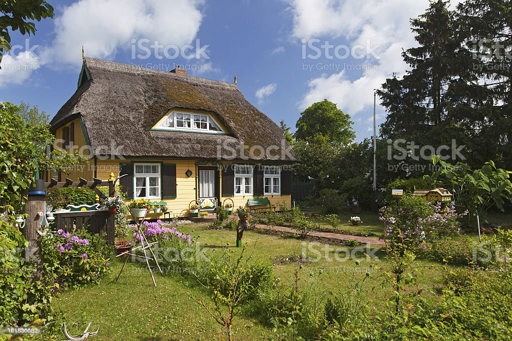 cottage with thatched roof and pretty garden stock photo