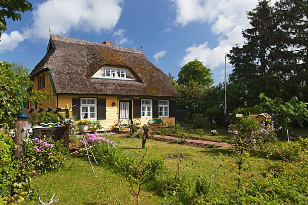 cottage mit strohdach und hübschen garten - strohdach stock-fotos und bilder