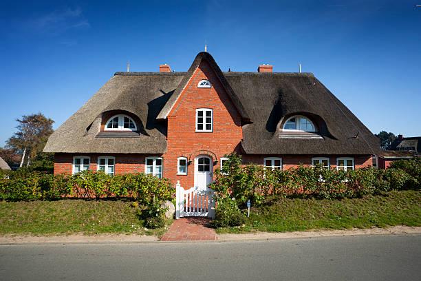 cottage mit strohdach stroh auf dem dach - strohdach stock-fotos und bilder