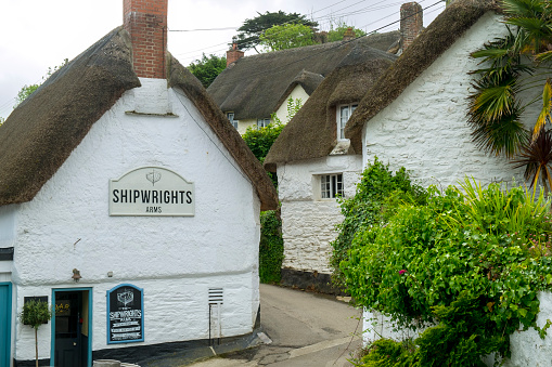 Cottages cluster around the public house in picturesque Helford village on the Helford Estuary