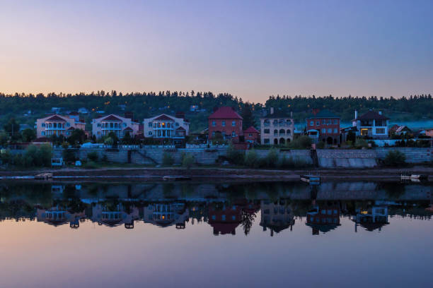 Cтоковое фото Cottages with reflection in the river in the evening