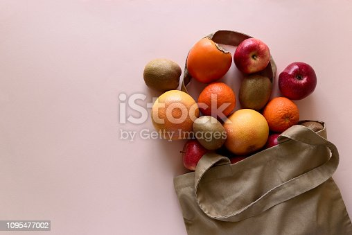 1126188273 istock photo Cotton bag with different fruits on pink background. Ecology pack for free plastic shopping. Top view. Flat lay 1095477002