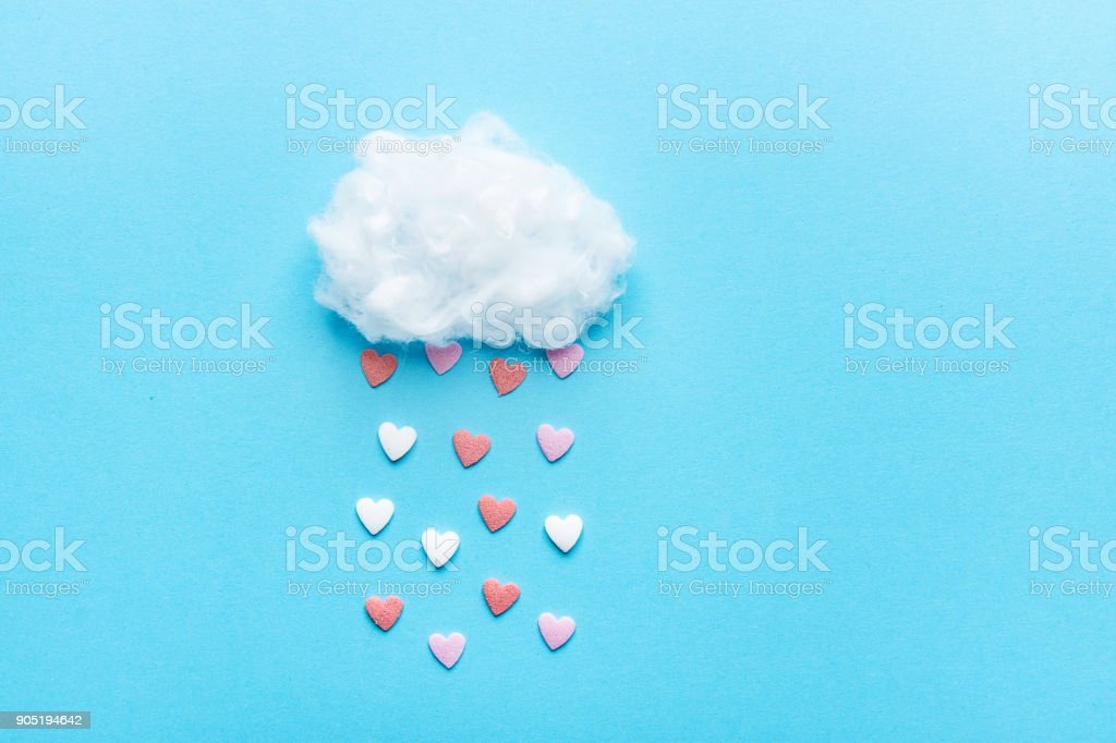 Cotton Ball Cloud Rain Sugar Candy Sprinkle Hearts Red Pink White on Blue Sky Background. Applique Art Composition Kids Style. Valentines Love Charity Concept. Greeting Card Poster Copy Space stock photo