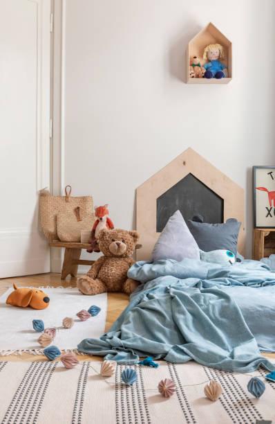wattebällchen und plüschtier neben blauen bett im kinderzimmer schlafzimmer innenraum mit teppich. echtes foto - fuchs kissen stock-fotos und bilder