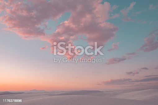 Pink cotton candy clouds stretch across the sky over the white sand dunes at sunset in White Sands National Monument, New Mexico, USA.
