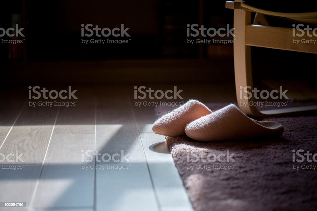 cotton slippers on carpet in sunlight stock photo