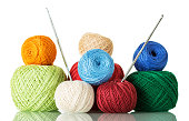 Cotton yarn balls of different shades and crochet hooks, isolated on white background