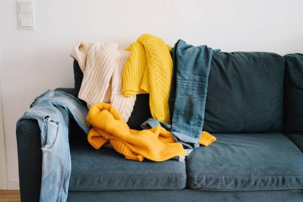 Couch mit unordentlicher Kleidung bedeckt – Foto