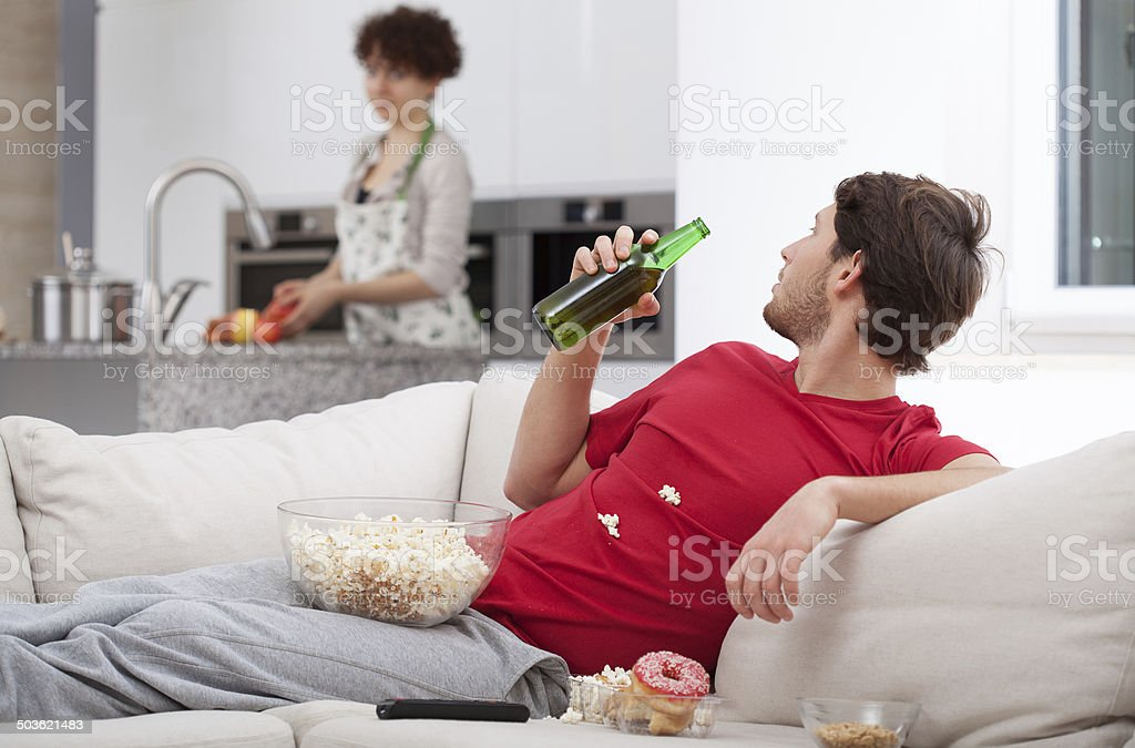 Couch potato doesn't help wife stock photo