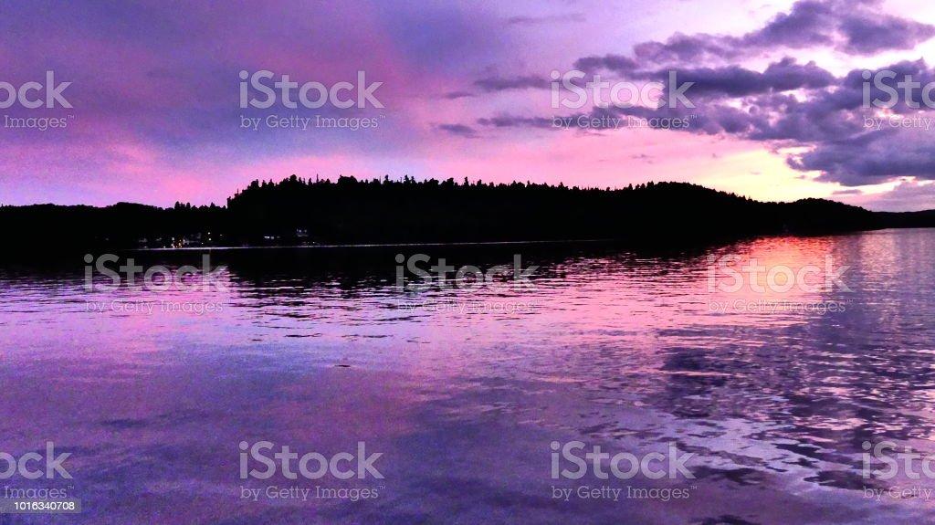 Couche de soleil rose et mauve sur l'eau avec silhouette de montagne stock photo