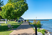 Tourists walking along the plank road by the lake.\nDuring summer weekend, many family come to Couchiching Beach Park to swim in Orillia Ontario, Canada.