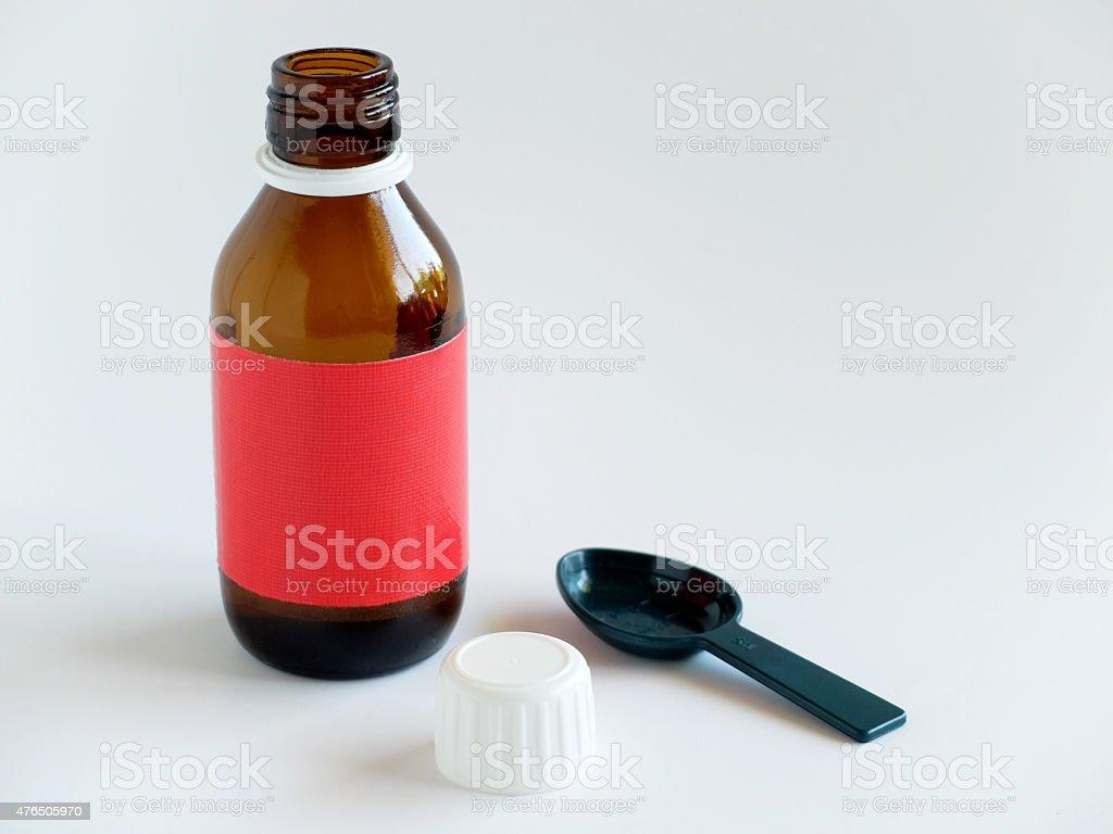 Jarabe para la tos botella y cuchara sobre fondo blanco. - foto de stock