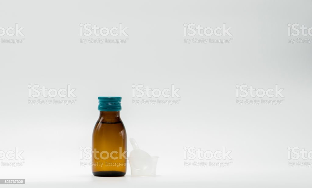 Cough syrup in amber bottle with blank label and a plastic measuring cup, teaspoon on white background stock photo