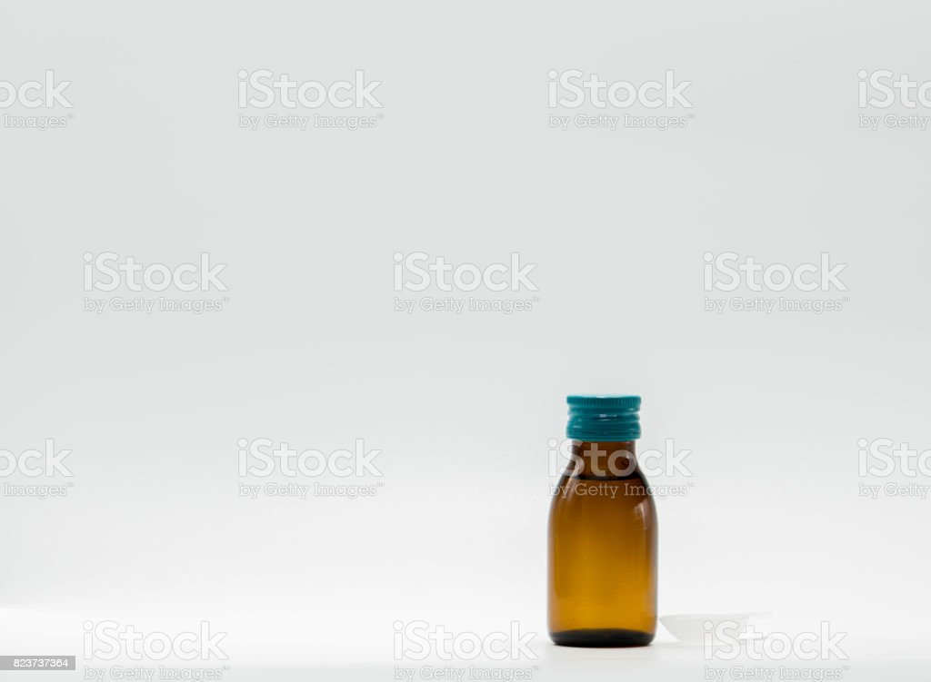 Cough syrup in amber bottle with blank label and teaspoon on white background stock photo