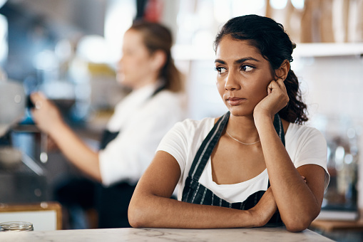 Shot of a young woman looking unhappy while working behind the counter of a cafe