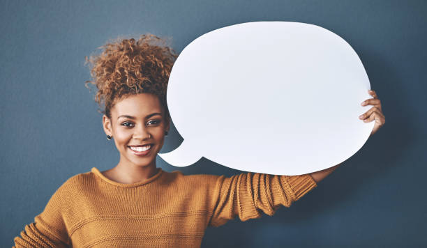 Could I have everyone's attention please Studio shot of a young woman holding a speech bubble against a grey background speech bubble stock pictures, royalty-free photos & images