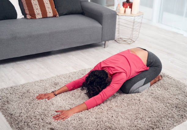 I could stay in this position forever Full length shot of an unrecognizable woman holding a child's pose while doing yoga in her living room at home childs pose stock pictures, royalty-free photos & images