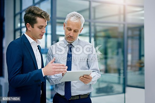 Cropped shot of two businessmen working together on a digital tablet in an office