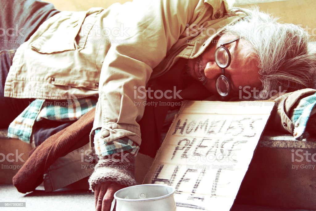 Could you please help homeless man sleeping on walkway street in the capital city. royalty-free stock photo