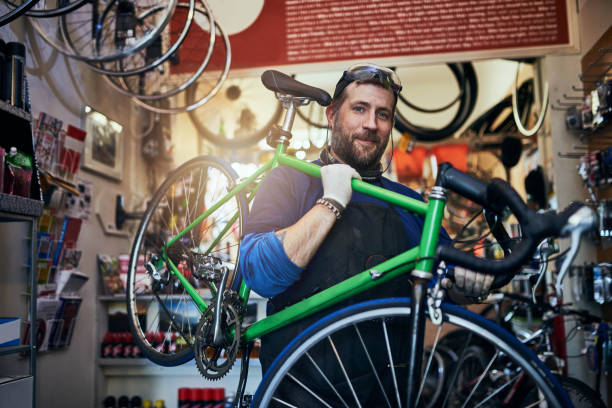 I couldn't imagine a better career for me Shot of a handsome man working in his self-owned bicycle workshop bicycle shop stock pictures, royalty-free photos & images