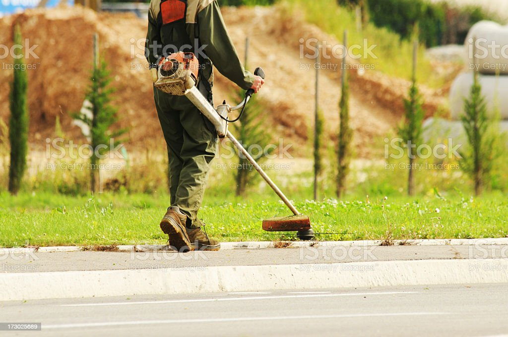 council worker strimming the grass verges stock photo