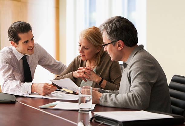 asesor va de periódicos con pareja de ancianos - planificación financiera fotografías e imágenes de stock