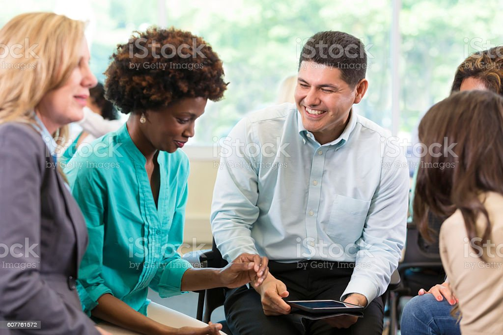 A counselor leads a group therapy session stock photo