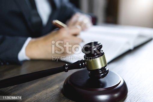 istock Counselor or Male lawyer working on courtroom sitting at the table. Legal law, Judge gavel with Justice lawyers advice with gavel and Scales of justice 1125288474