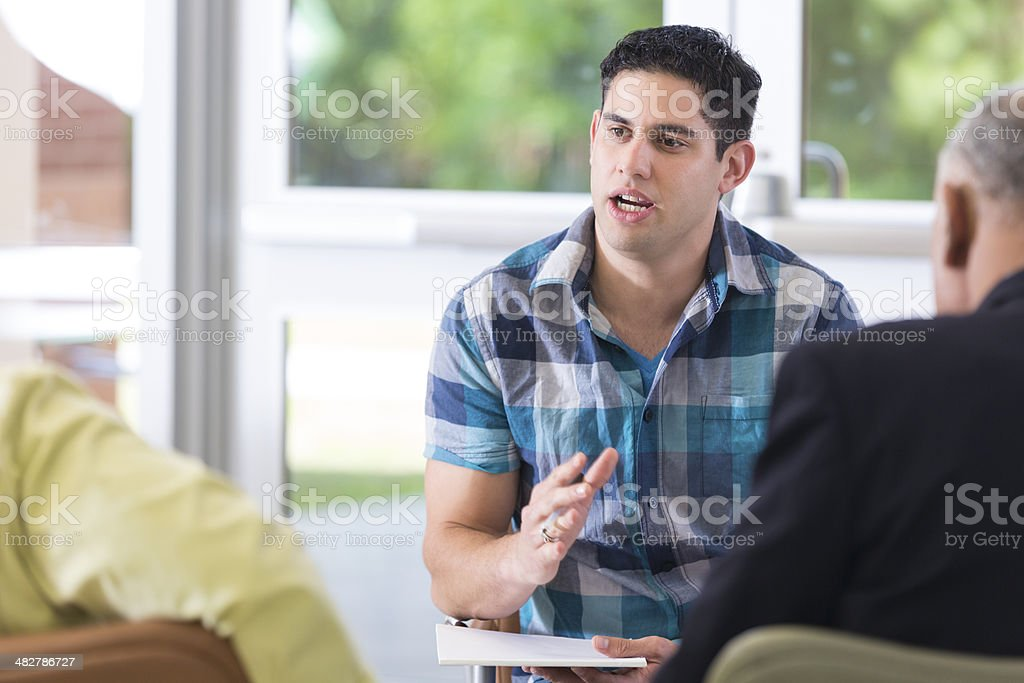 Counselor speaking to couple in therapy session stock photo