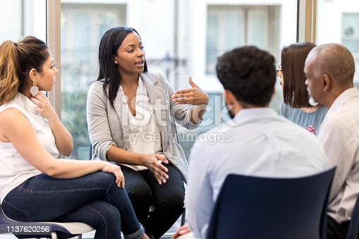 A young female counselor gestures as she sits in a circle with clients during a group therapy session and speaks.  She is looking at the female client next to her.