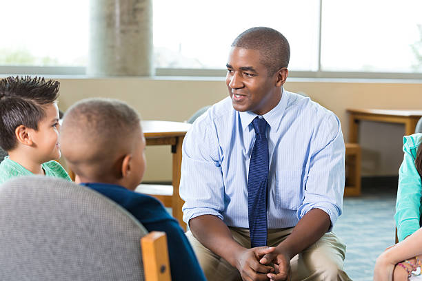 counselor talking to elementary age students during after school program - school counselor stock pictures, royalty-free photos & images