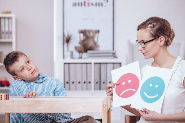 Counselor teaching autistic kid stock photo