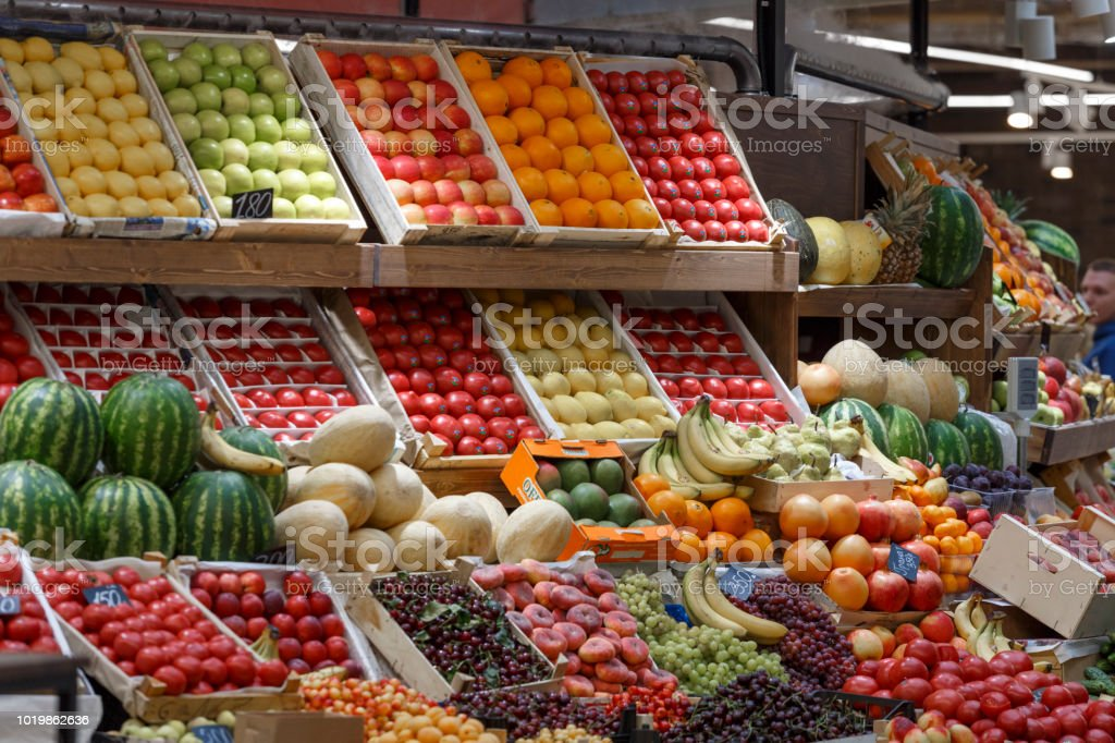 Counter at the market with vegetables and fruit. Vegetables and fruits are arranged in boxes stock photo