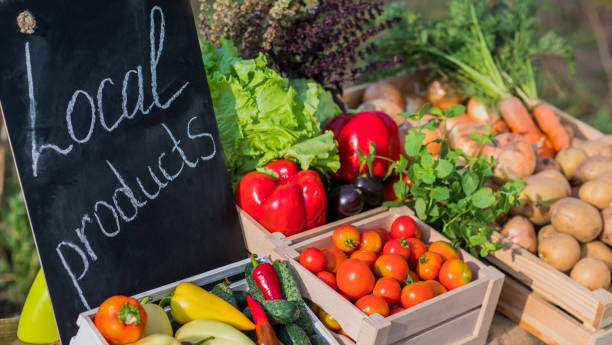counter with fresh vegetables and a sign of local products - farmers market stock pictures, royalty-free photos & images