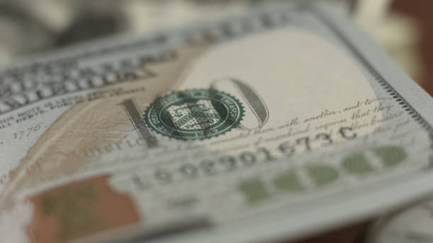 Counterfeit money detection, one hundred dollar bill closeup, banking concept Counterfeit money detection, one hundred dollar bill closeup, banking concept us currency stock pictures, royalty-free photos & images