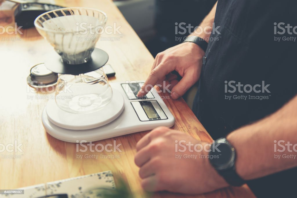 Counterman weighing grains for making hot beverage stock photo